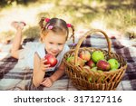little girl with apples in park | Shutterstock . vector #317127116