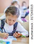 schoolgirl sits at a school... | Shutterstock . vector #317243315