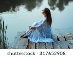 Girl Sitting On A Wooden Pier...