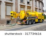 sewage truck on city street in...