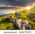 white sharp boulders on the grassy hillside on the peak on high mountain range at sunset - stock photo