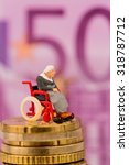 Small photo of woman in wheelchair on money stack, symbol photo for disability, attendance allowance and expenses public health