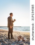 Stock photo young caucasian male drinking coffee on beach while walking with dog during sunrise 319154585