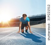 Small photo of Fit and confident man in starting position ready for running. Male athlete about to start a sprint looking at camera with bright sunlight.