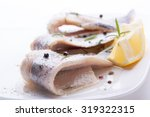 Herring with salt, pepper, herbs and lemon on white ceramic plate on white background