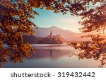 Stock photo little island with catholic church in bled lake slovenia at sunrise with castle and mountains in 319432442