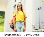 Small photo of Fashion portrait trendy young woman wearing a sunglasses and t-shirt with backpack in the city