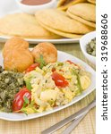 Small photo of Ackee & Saltfish - Traditional Jamaican dish made of salt cod and ackee fruit. Served with callaloo and johnny cakes. Patties on background.