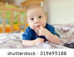 baby boy with finger in mouth | Shutterstock . vector #319695188
