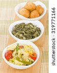 Small photo of Ackee & Saltfish - Traditional Jamaican dish made of salt cod and ackee fruit. Served with callaloo and johnny cakes.