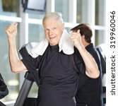 Small photo of Old man on treadmill in fitness center holding his thumbs up