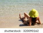 young lady with hat on a sandy...   Shutterstock . vector #320090162