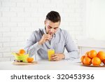 young man drinking orange juice | Shutterstock . vector #320453936
