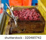 Small photo of wooden box filled with lobster bands and a bander