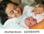 new born baby with mother in... | Shutterstock . vector #320584595