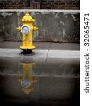 Yellow fire hydrant on sidewalk reflected in puddle of water - stock photo