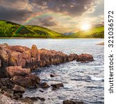 composite image of summer landscape  on lake with rocky shore and some boulders near forest under the rainbow  in mountain  with high peak far away in evening light - stock photo