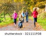 family taking walk in autumn... | Shutterstock . vector #321111938