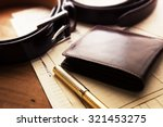 Small photo of Documents, pen, belt and a leather wallet on a wooden desk. hotel table or gentleman's desk. shallow depth of field.