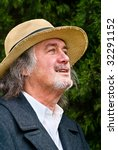 Small photo of The Happy Honcho - Middle aged man with long hair and old straw hat laughing and enjoying life
