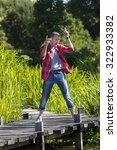 Small photo of celebrating success outdoors concept - extrovert middle age man with casual checked shirt dancing for fun achievement on bridge near water,natural summer daylight
