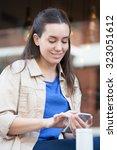 pretty woman drinking coffee in ... | Shutterstock . vector #323051612