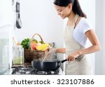 Woman Standing By The Stove In...
