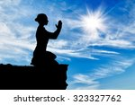 silhouette of praying woman on... | Shutterstock . vector #323327762
