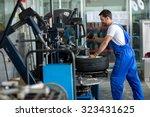 repairman balancing  car wheel... | Shutterstock . vector #323431625