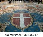 Walking on mosaic in gallery Vittorio Emanuele II in Milan, Italy - stock photo