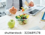 Businessman having a lunch break at desk, he is eating fresh salad and holding a cracker, unrecognizable person - stock photo