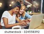 Two multiracial young female friends surfing the internet together on a laptop as they sit in a cafeteria enjoying a cup of coffee - stock photo