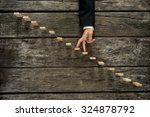 Small photo of Businessman walking his fingers up wooden steps or pegs resembling a staircase mounted in rustic wooden boards in a conceptual image of success, promotion and advancement.