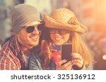 couple doing selfie outdoors.   Shutterstock . vector #325136912