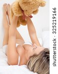 Small photo of Happy pregnant woman holding a teddy bear up