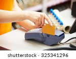 Small photo of sale assistant cashier accepting credit bank card and using payment terminal for purchase