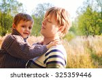 dad and son in autumn park.... | Shutterstock . vector #325359446