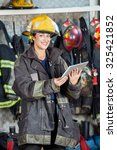 Small photo of Portrait of happy firewoman in uniform holding digital tablet at fire station