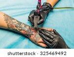 close up tattoo artist...   Shutterstock . vector #325469492