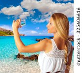 Small photo of Blond tourist in Mallorca taking photos of Cala Agulla photomount
