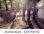 young man picking up trash... | Shutterstock . vector #325756742