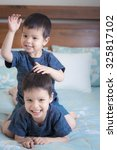 Small photo of 2 cute mixed race Asian Caucasian brothers play cheekily together inside on a bed