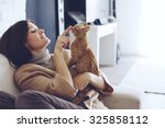 Stock photo young woman wearing warm sweater is resting with a cat on the armchair at home one autumn day 325858112