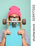 Small photo of Be yourself. Agreeable curious young girl holding her skateboard with both hands and looking out of it while standing isolated on blue background