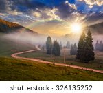 road on through the meadow near few fir trees and forest in foggy mountains in evening light - stock photo