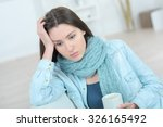 sad woman holding a mug of... | Shutterstock . vector #326165492
