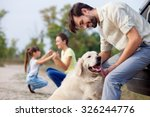 Stock photo cheerful friendly family is resting in park the man is playing with dog and leaning on car the 326244776