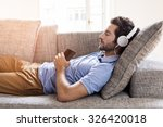 man at home on sofa listening a ... | Shutterstock . vector #326420018