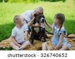 Stock photo sister and brothers playing with american staffordshire terrier on a lawn 326740652
