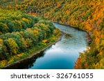 Upper Delaware river bends through a colorful autumn forest, in Hawk